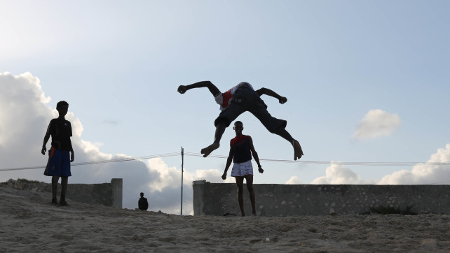 Somali man playing summersault at liido beach Mogadishu Somalia on August 10, 2015 photography by Feisal Omar